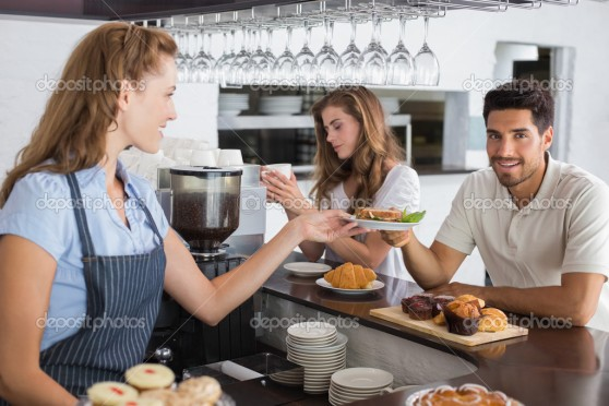 Friendly female cafe owner giving sandwich to a man at the coffee shop